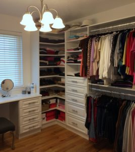 Custom Closet with a bedroom vanity, adjustable corner shelves, drawers and organized hanging.